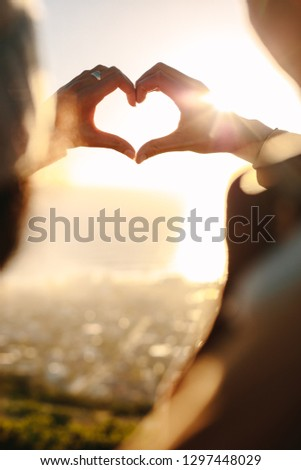 Close up of young couple in love making a heart with their fingers in bright sunlight. Romantic couple gesturing a finger heart.
