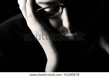 Close-up of young despaired man contemplating, low key, black and white