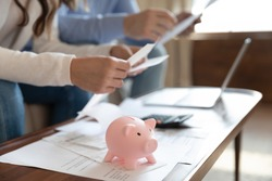 Close up of young family sit at desk manage household finances save money in piggy bank for future, couple consider home financial paperwork documents together, feel economical about expenses