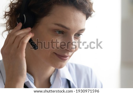 Close up of young female doctor in headset talk consult patient on video call in modern hospital. Smiling Caucasian woman GP or therapist in earphones have webcam consultation or virtual event.