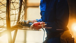 Close Up of Young Female Fabricator in Blue Jumpsuit. She is Grinding a Metal Tube Sculpture with an Angle Grinder in a Studio Workshop. Empowering Woman Makes Modern Abstract Metal Artwork.