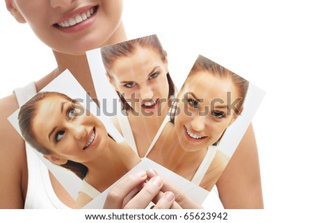 Close-up of young female holding three images of herself