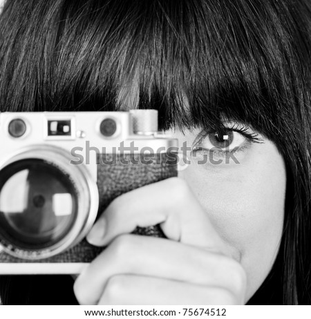 Close up of young girl in black and white with vintage camera