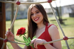 Close-up of young girl with red rose in a public park.