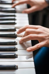 Close up of young girls hands, playing the keys