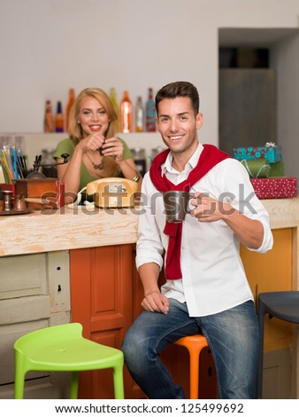 close-up of young handsome caucasian guy smiling with a coffee mug in his hand with a blonde girl behind the counter of a colorful cafe