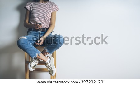 Close-up of young hipster girl wearing blue ripped jeans and using modern smartphone on a blank white background with copy space for your content, stylish woman sitting on a chair and using cellphone