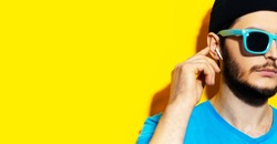 Close-up of young hipster using wireless earphones/earbuds, touching it with finger. Wearing cyan shades, blue shirt and black beanie hat. Studio background of yellow color with copy space.