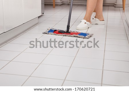 Close-up Of Young Maid In Uniform Cleaning Kitchen Floor