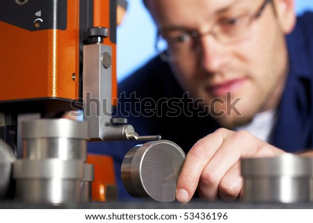 Close-up of young male engineer in blue overall taking precision measurement of metal parts with micrometer, isolated on blue background. #53436196