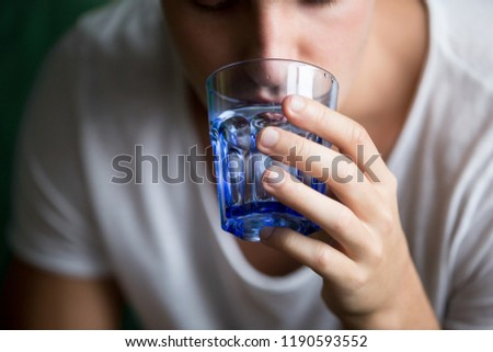 Close up of young man feeling thirst holding transparent blue glass drinking still water, focus on arm. Dehydration of organism or health care, good habit and weight loss. Hangover after party concept