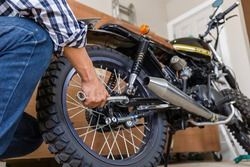 Close-up of Young man hand fixing motorcycle, Mechanical hobby and repairs concept.