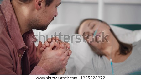 Close up of young man holding hand of sick mother sleeping in hospital bed. Adult son visiting ill senior mom resting in bed with nasal oxygen tube in ward at clinic Foto d'archivio ©