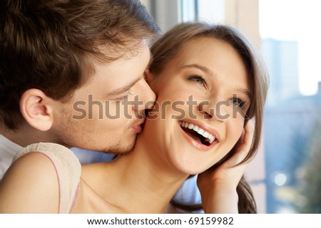 Close-up of young man kissing happy woman