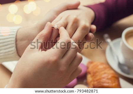 Close up of young man putting on girlfriend finger engagement ring during romantic dinner at cozy french cafe. Marriage proposal for beloved woman. Young engaged couple. Wedding proposal concept
