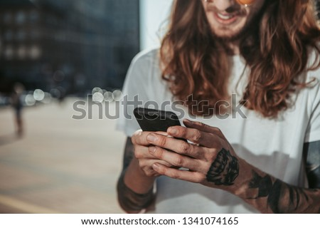 Close up of young man reading messages on smartphone. Focus on male hand with black mobile phone