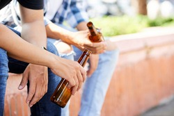 Close-up of young men holding bottles of beer while sitting outdoors