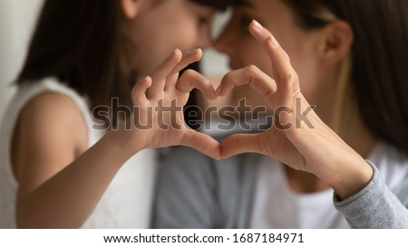 Close up of young mother and cute little daughter make heart sign with hands enjoy close tender moment together, caring mom and grateful small girl child show love and support in family relationships