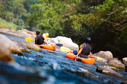 Close-up of young people rafting on the river turbulent flow. Extreme and enjoyment sport.