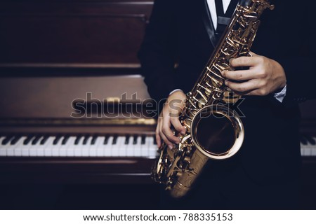close up of Young Saxophone Player hands  playing alto sax musical instrument over piano  background  ,  closeup with copy space, vintage tone,  can be used for music background