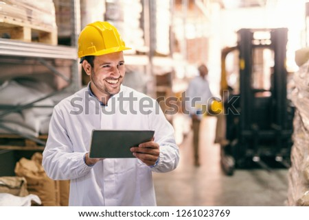 Close up of young smiling bearded man with protective helmet on head using tablet while standing in warehouse.