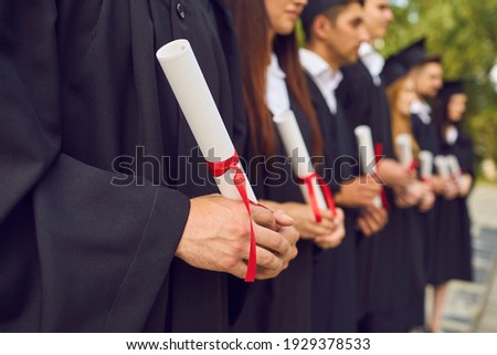 Close-up of young university graduates hands holding diplomas after university graduating outdoors, selective focus. Graduating from university or college concept