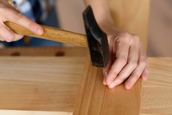 close up of young woman assembling furniture at home working with hammer. DIY concept. High quality photo