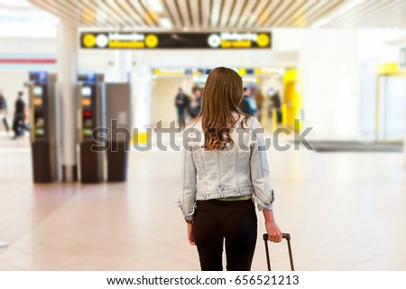 Close-up of young woman back side at the airport, carrying her trolly bag.