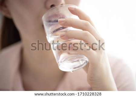 Close up of young woman drinking glass of water