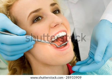Close-up of young woman during inspection of oral cavity with help of hook and mirror