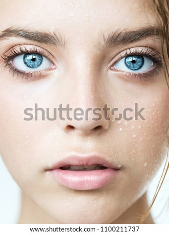 Close up of young woman face  with clean perfect skin and water moisture drops. Macro portrait of beauty model with natural nude makeup moisturizing her skin by lotion. Spa, skincare and wellness. #1100211737