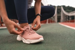 Close up of young woman getting ready for jogging outdoors while lacing her pink sneakers. Health and sport concept