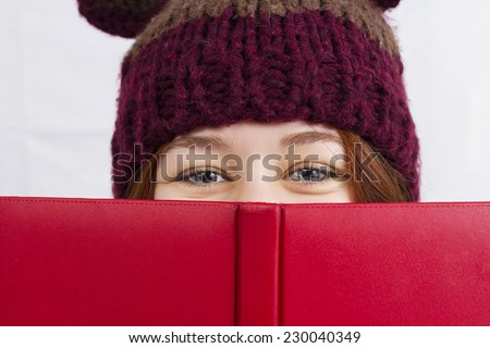 Close up of young woman holding red  book or diary wearing a winter hat looking like a head bear isolated on white background.