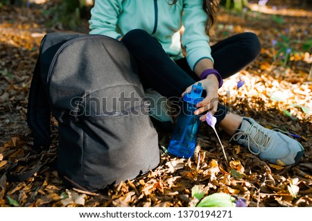 Close-up of young woman in the forest, resting, with backpack and a bottle of water at sunset in the autumn season. #1370194271