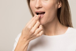 Close up of young woman isolated on grey background take medicine antidepressant or birth control pill, female put tablet in mouth have painkiller or antibiotic. Healthy lifestyle, medication concept