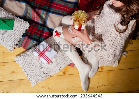 Close-up of young woman legs holding gift box, lying on carpet at the Christmas tree over living room.