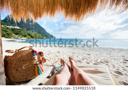 Close up of young woman legs relaxing at tropical sandy beach