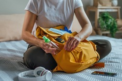 Close up of young woman packing her backpack with hand sanitizer. Prepairing for a travel after the end of quarantine. New life after Pandemic COVID-19 concept.
