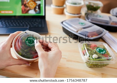 Close-up of young woman putting a sticker on a box of food while sitting at wooden table Foto stock ©