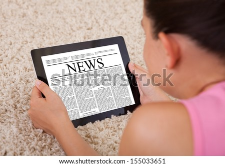 Close-up Of Young Woman Reading A News Article On Digital Tablet