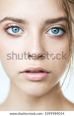 Close up of young woman's face with clean perfect skin and water moisture drops. Portrait of beauty model with natural nude makeup moisturizing her skin by lotion. Spa, skincare and wellness.