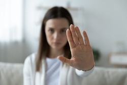 Close up of young woman show stop gesture sign by hand saying no to domestic violence or abuse, determined millennial female protest against abortion or discrimination, nonverbal language concept