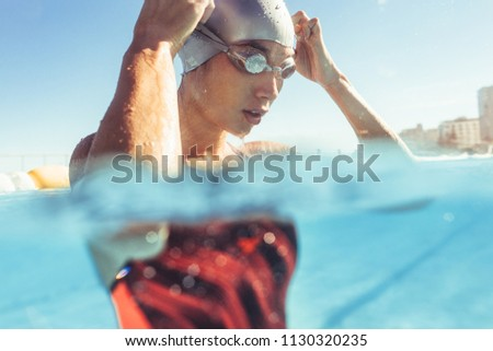 Close up of young woman swimmer inside the pool adjusting her goggles. Professional swimmer taking a break while training in outdoor pool.