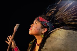 close up of young woman Teotihuacana, Xicalanca - Toltec in black background, with traditional dress dance with a trappings with feathers and drum