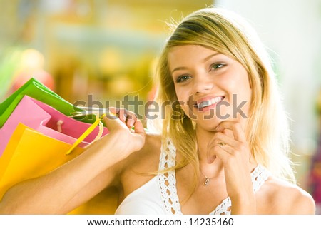 Close-up of young woman touching her chin by hand and looking aside in the shopping mall