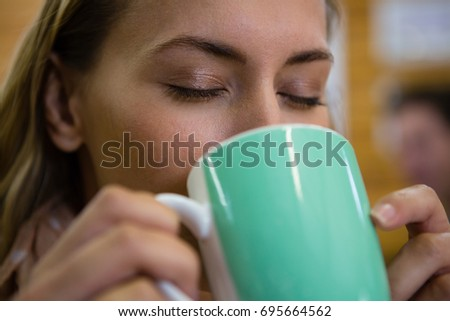 Close up of young woman with eyes closed drinking coffee at cafe