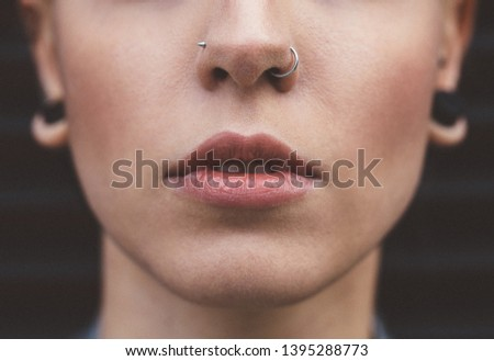 fee4e54428222 Close up of young woman with nose piercings