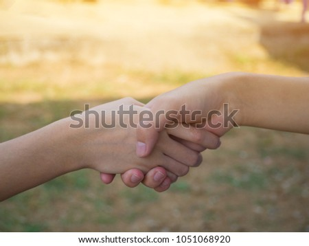 Close-up of young women are handshake with nature background in the garden. Friendship day. Teamwork concept #1051068920