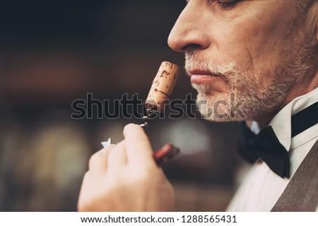 Close up. Old experienced sommelier smells wine stopper on corkscrew, assessing taste of drink. Wine tasting. #1288565431