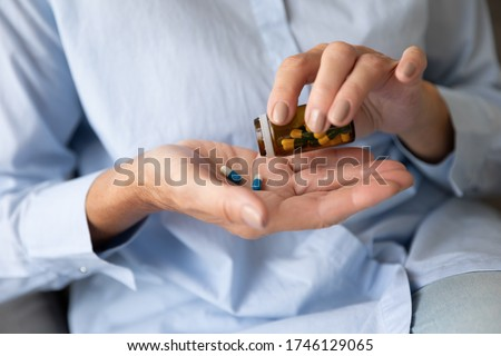 Close up old female hands holds glass bottle pours pills on palm taking daily dosage of medication, problem prevention, meds treat symptoms of Alzheimer, chronic senile diseases cure therapy concept Stock photo ©